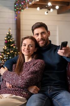 Man and woman watching tv on christmas