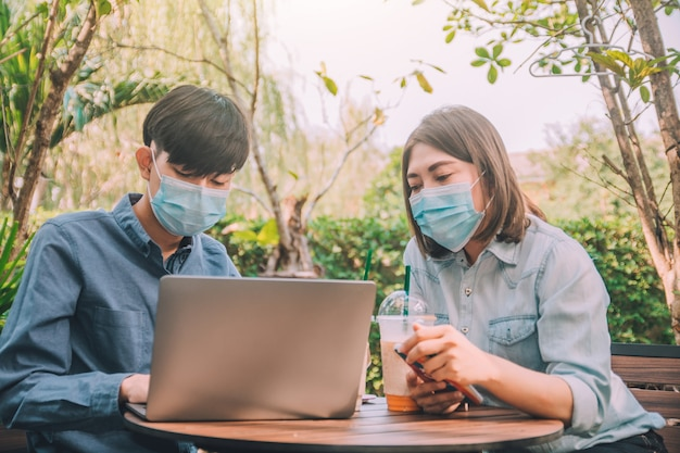 Man woman wear mask sitting outdoor lifestyle using computer technology