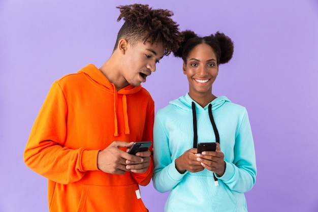 Man and woman wearing colorful sweatshirts using mobile phones, isolated over violet wall