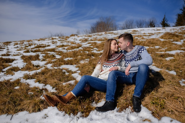Man and woman wearing knitted clothing hugging on snowy mountain.