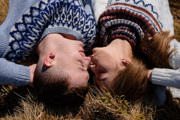 Man and woman wearing knitted clothing kissing on snowy mountain.