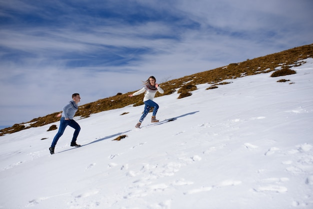 Man and woman wearing knitted clothing playing on snowy mountain.