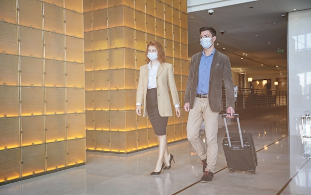 Man and woman wearing medical masks while walking with their luggage in a hotel hall