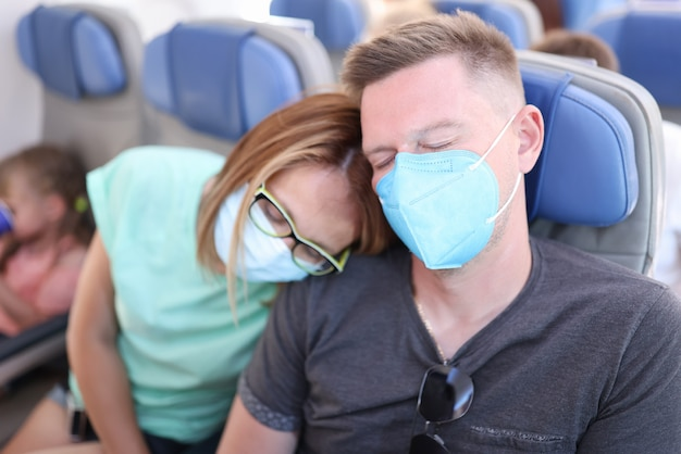 Man and woman wearing protective respirators are flying in airplane