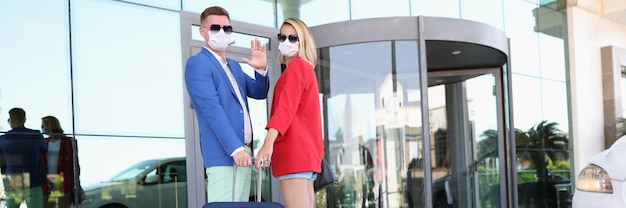 Man and woman wearing sunglasses and protective medical masks with suitcase near building