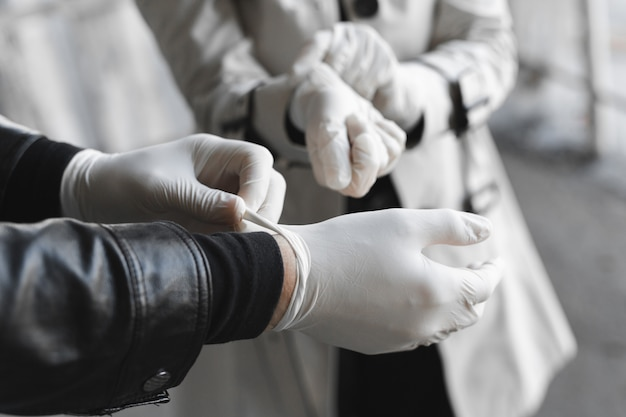 Man and woman wears medical gloves to be safe from the outbreak of novel coronavirus. wearing hand gloves can prevent the covid-19 coronavirus