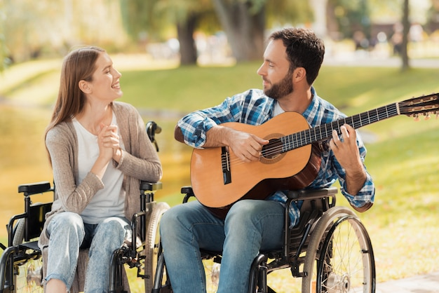 A man and a woman in wheelchairs met in the park