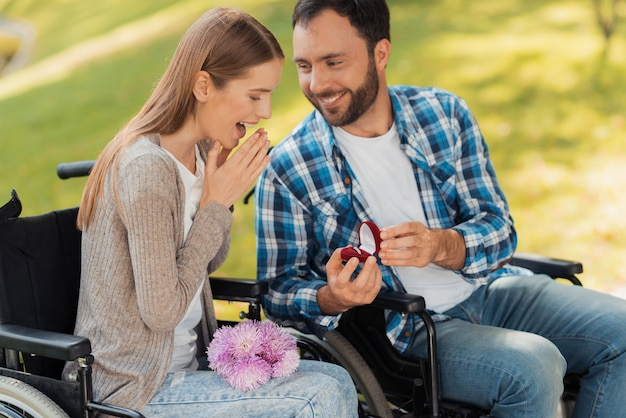 A man and a woman in wheelchairs met in the park.