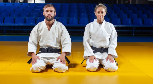 Man and woman in white kimono with a black belt sit on the floor and meditate in the sports hall. oriental martial arts, judo