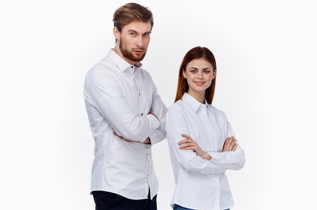 A man and a woman in white shirts with their arms crossed are standing behind each other employees