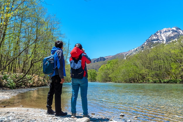 Man and woman with azusa river and mount yake at kamikochi in northern japan alps.