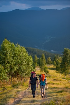 Man and woman with backpacks climbing up along a beautiful mountain area