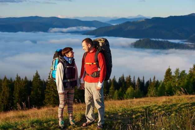 A man and a woman with backpacks look at each other in the rays of a sunset against the backdrop of the beautiful scenery of the forest, mountains and mist lying on them