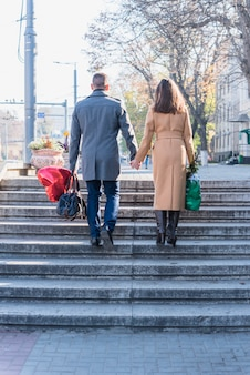 Man and woman with bags going up on stairs on street