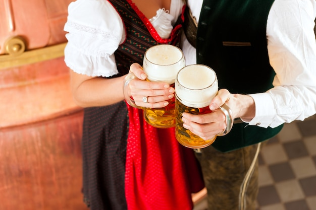 Man and woman with beer glass in brewery