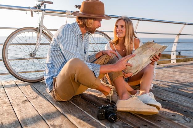 Uomo e donna con moda stile hipster boho capelli biondi divertirsi insieme, guardando nella mappa visite turistiche