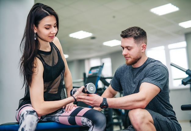 Man and woman with dumbbells flexing muscles in gym
