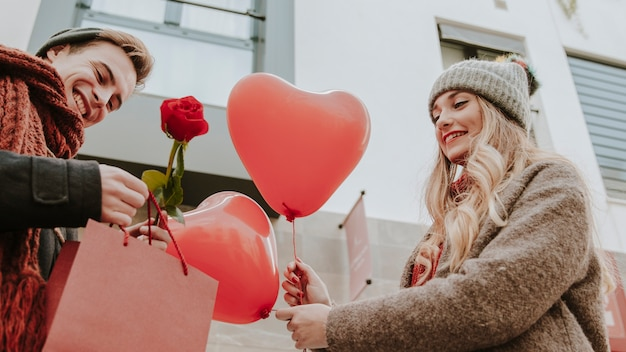 Man and woman with gifts and heart balloons