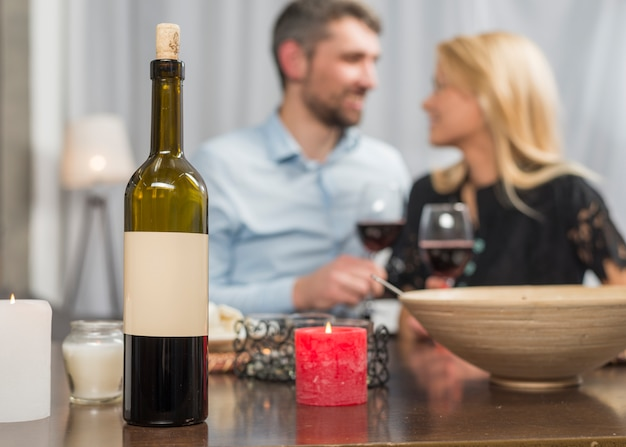 Man and woman with glasses at table with bottle and bowl