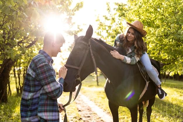 Uomo e donna con cavallo tiro medio