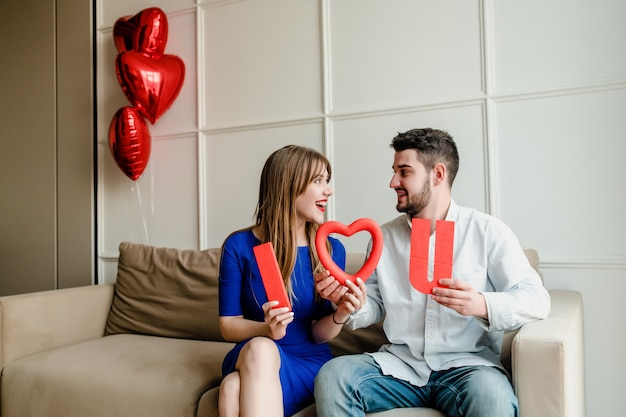 Man and woman with i love you letters on couch at home with heart shaped balloons