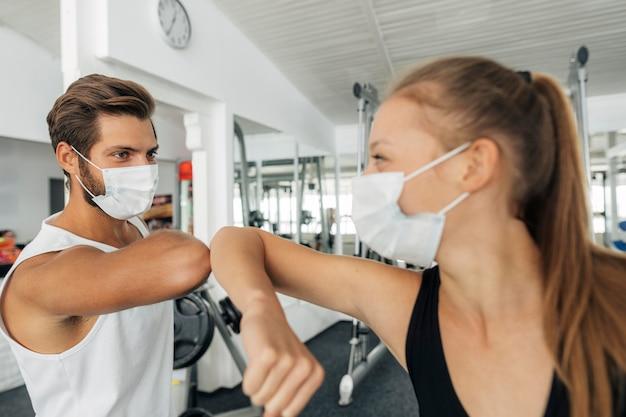 Uomo e donna con maschere mediche che fanno il saluto di gomito in palestra