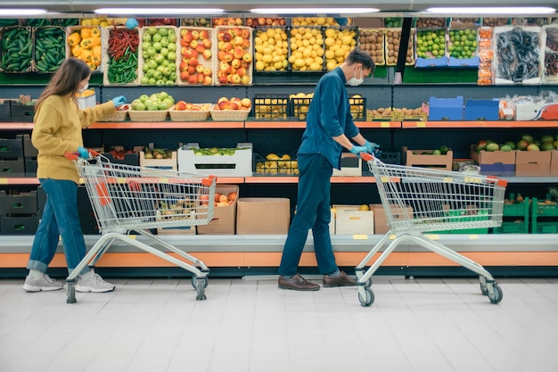Man and a woman with shopping carts in a supermarket during the quarantine period. photo with a copy-space