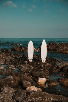 Man and woman with surf boards holding hands on rock coast