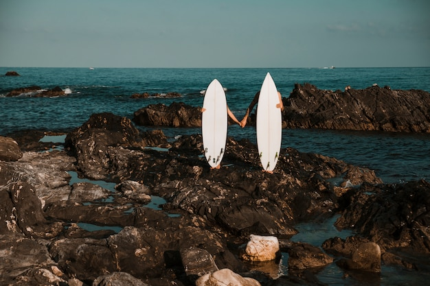 Man and woman with surf boards holding hands on stone coast