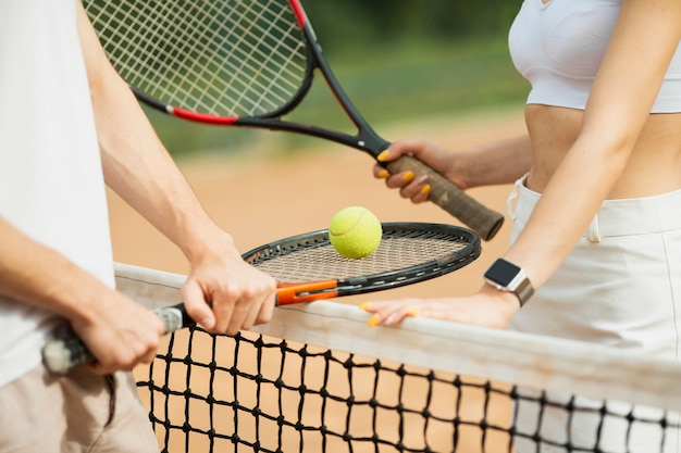Man and woman with tennis rackets