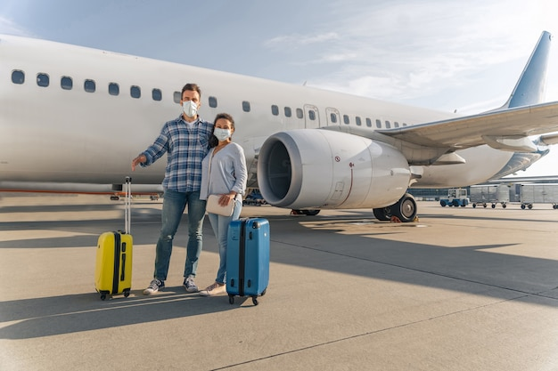 Man and woman with travel bags stansing near plane