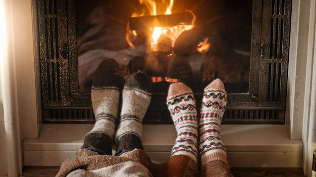 Man and woman in woolen socks warming feet at burning fireplace