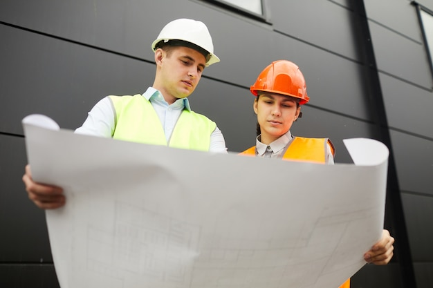 Man and woman in work helmets holding blueprint of new building and examining it in team while standing outdoors