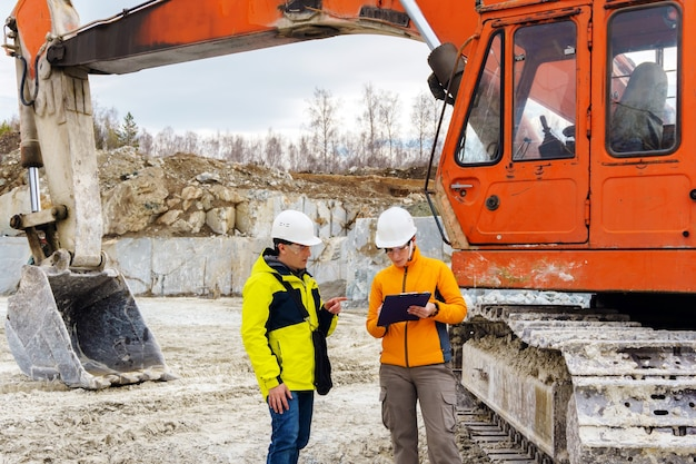 A man and a woman workers or geologists in helmets sign a document against the background of construction equipment in a quarry
