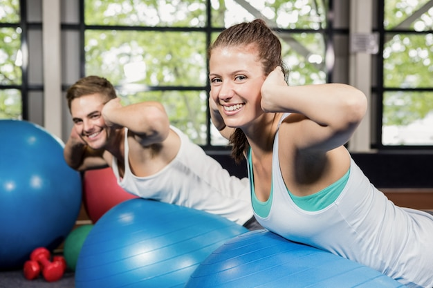 Man and woman working out on fitness ball