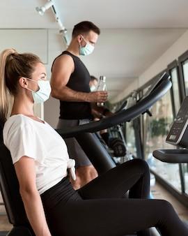 Uomo e donna che lavorano in palestra con maschere mediche