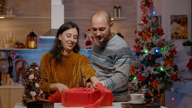 Man and woman wrapping red paper on present for christmas