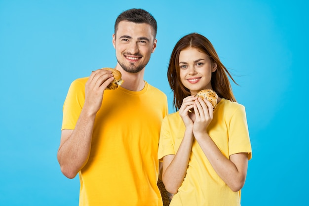 Man and woman in yellow tshirts with hamburgers in their hands fast food