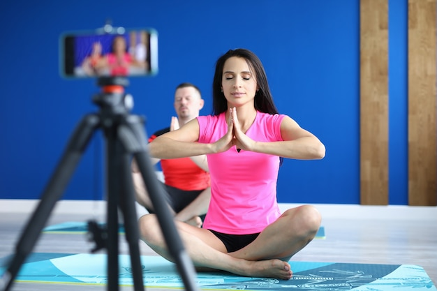 Man and woman do yoga and take training on phone