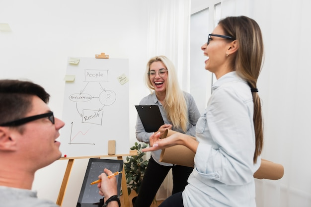 Man and women laughing at office