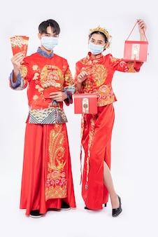 Uomo e donna indossano maschera e cheongsam con in mano denaro regalo rosso e borsa rossa