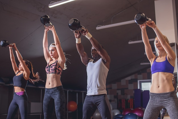 Man and women with coach at kettlebell functional training in fitness center