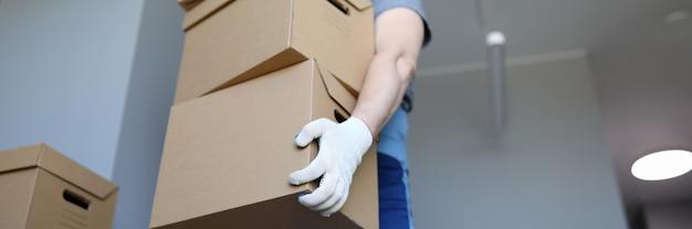 男の作業服と手袋は段ボール箱を運ぶ