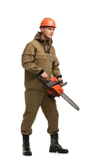 Man in work clothes and protective helmet holding power saw isolated full-length view