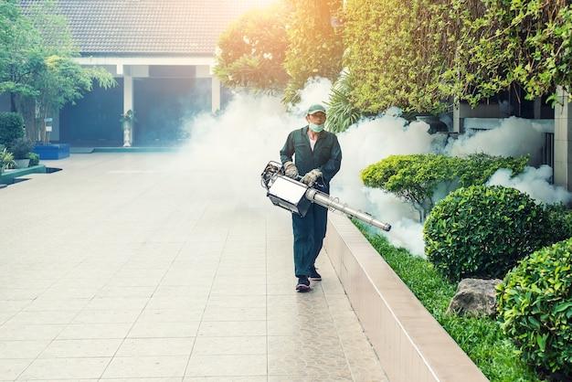 Человек работает туман для устранения комаров для предотвращения распространения лихорадки лихорадки денге и вируса зики