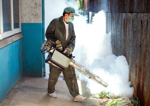 Человек работает туман, чтобы устранить комаров для предотвращения распространения лихорадки денге и вируса зика