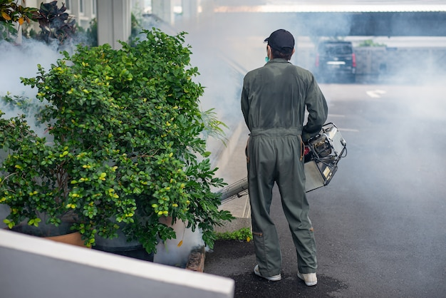 Человек работает противотуманки для устранения комаров для предотвращения распространения лихорадки денге