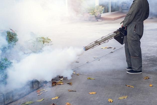 Человек работает туман, чтобы устранить комаров для предотвращения распространения лихорадки денге