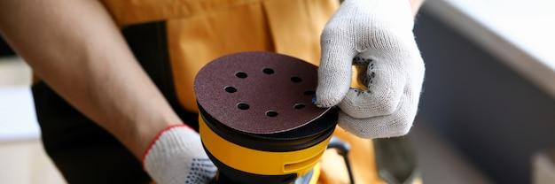 Man in work gloves holds tool sander machine