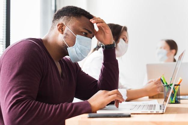 Uomo al lavoro in ufficio durante una pandemia con maschera facciale